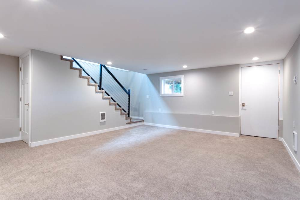 basement finishing with carpet and grey tones